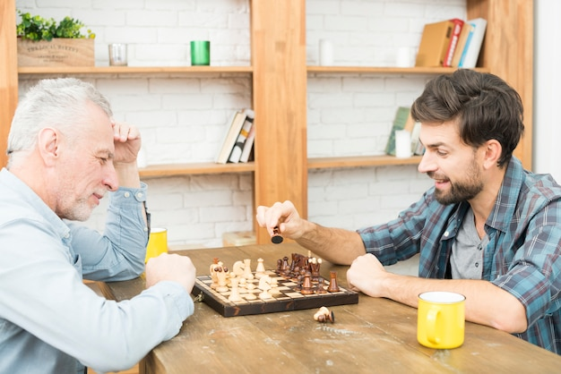 Aged man and young guy playing chess at table in room
