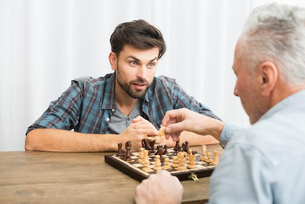 Aged man and young guy playing chess at table
