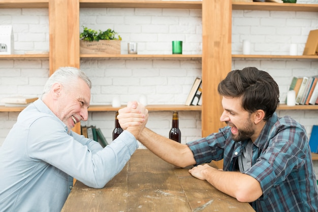 Aged man and young guy with hands clasped in arm wrestling challenge at table in room