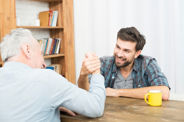 Aged man and young happy guy with hands clasped in arm wrestling challenge at table in room