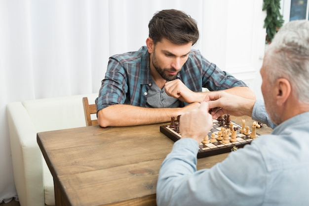 Aged man and young pensive guy playing chess at table in room