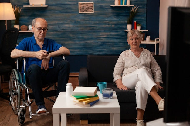Пожилая супружеская пара отдыхает в гостиной перед телевизором