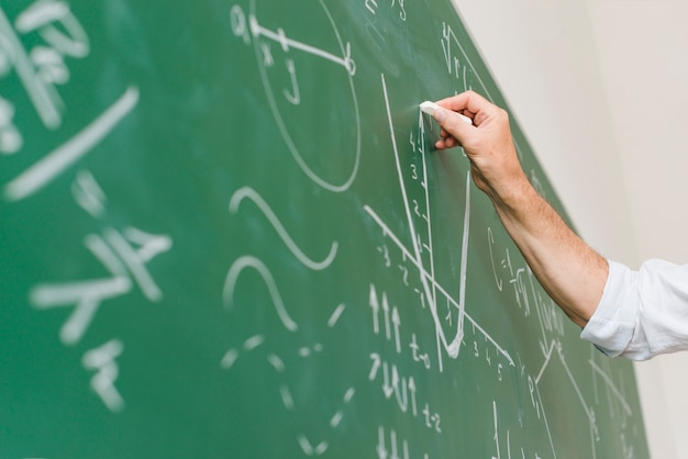 高齢者の数学の先生が黒板に図を描く