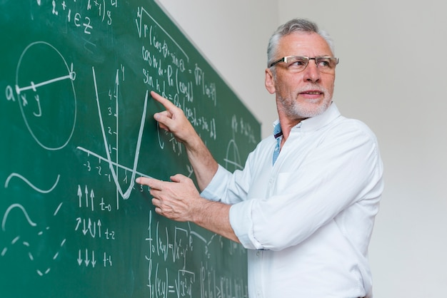 Aged math teacher explicating function at classroom