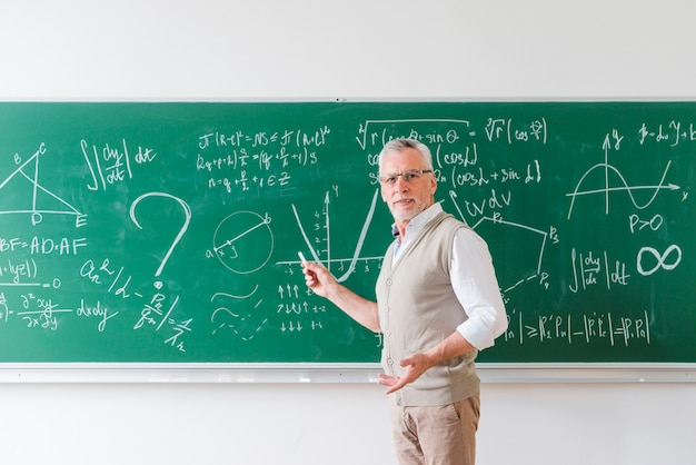 Aged math teacher pointing with chalk at blackboard