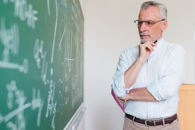 Aged math teacher thinking next to chalkboard