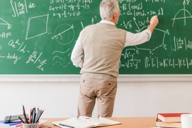 Aged math teacher writing equation on chalkboard