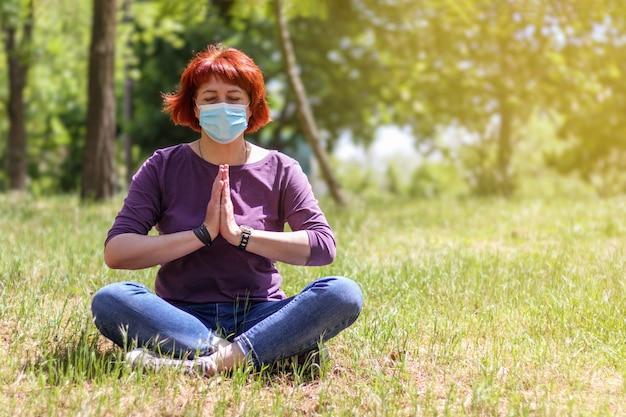 의료용 마스크를 쓰고 공원에서 요가를 하고 연꽃 자세로 파드마사나를 하고 있는 성숙한 여성. 빨간 머리를 가진 잘 나이 든 여자.
