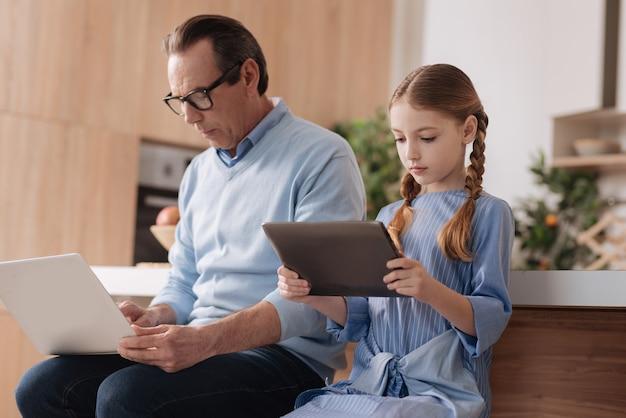 실내에 앉아 인터넷을 서핑하고 소셜 미디어 프로필을 확인하는 동안 손녀와 함께 기기를 사용하는 노령의 움직이지 않는 은퇴 한 남자