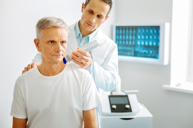 Престарелый пациент. хороший приятный пожилой мужчина посещает терапевта и проходит медицинское обследование, заботясь о своем здоровье