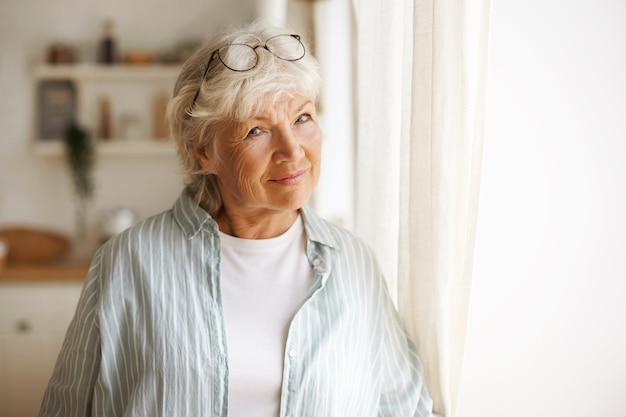 Aged people, maturity, retirement and lifestyle concept. indoor image of casually dressed elderly mature female with gray hair standing by window, wearing glasses on her head, feeling lonely