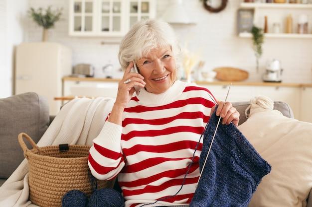 高齢者、退職、レジャー、現代技術の概念。リビングルームのソファでスカーフを編んでいる間、携帯電話で彼女の孫娘と話している白髪の美しい幸せなおばあちゃん