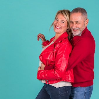 Aged positive man hugging from back laughing woman