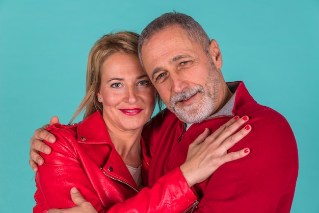 Aged positive man hugging with attractive woman