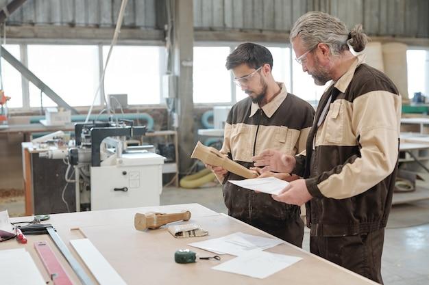 Престарелый профессиональный инженер, объясняя свой молодой стажер эскиз деревянной заготовки на встрече за большим столом в мастерской фабрики