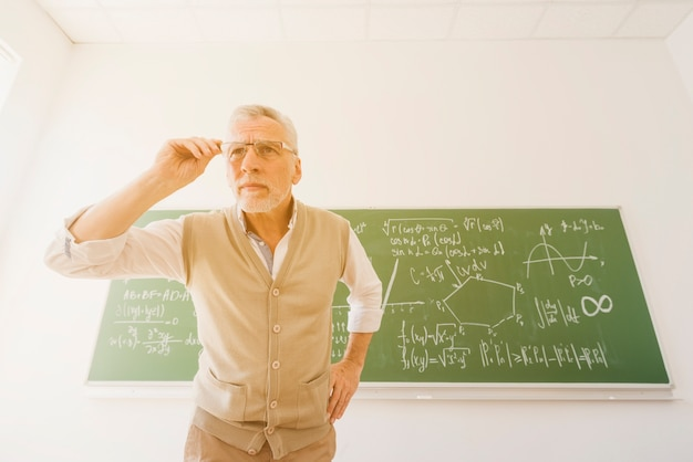 Aged professor looking through glasses in classroom