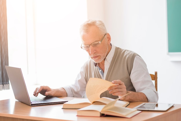 Aged professor male working with laptop while reading book in classroom