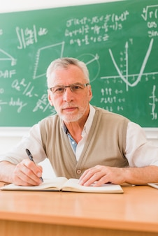 Aged professor writing in lecture room
