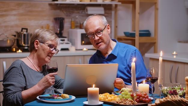 Пожилые, пенсионеры, пара, делающая покупки в интернете во время романтического ужина с помощью ноутбука. старики сидят за столом, просматривают, используют технолоты, интернет, отмечают годовщину в столовой.