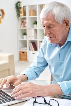家庭環境でオンラインデータのためにネットサーフィン中にラップトップのキーパッドのキーを押す青いシャツを着た老人