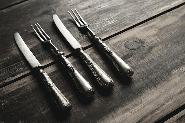 Set vintage retrò invecchiato di forchette e coltelli in acciaio inossidabile ricoperti di patina isolata sulla vista laterale del tavolo in legno nero spazzolato