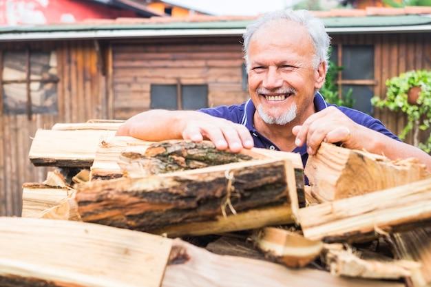 年配の男性が微笑み、冬に備えて薪を燃やし、暖炉やストーブで家を暖める