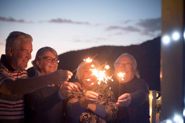 高齢者の友人は、夜に線香花火で楽しんで祝います
