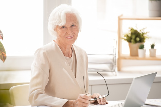 Aged smiling businesswoman in white elegant suit looking at you while sitting by desk in front of laptop in office