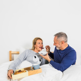 Aged smiling man giving berries to woman in duvet near breakfast on tray on bed