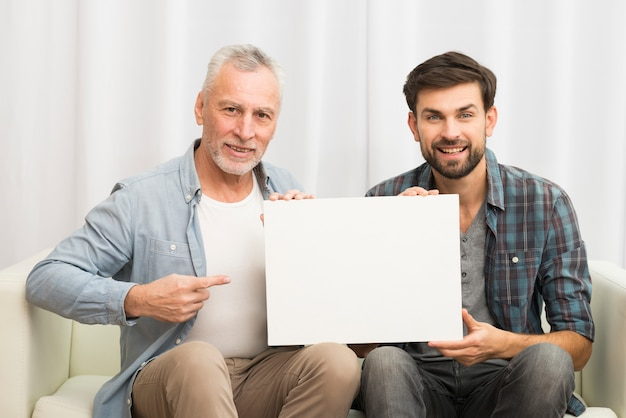 Aged smiling man pointing at paper and young happy guy on sofa