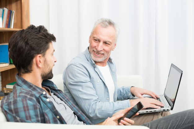 Aged smiling man with laptop and young guy using smartphone on sofa