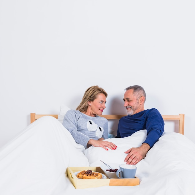 Aged smiling man and woman in duvet on bed near breakfast on tray