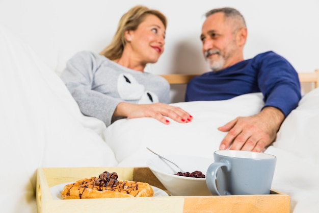 Aged smiling man and woman in duvet near breakfast on tray on bed