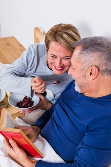 Aged smiling woman giving berries to man with book on bed