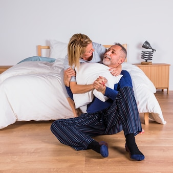 Aged smiling woman hugging man with pillow near bed