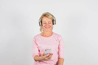 Aged smiling woman in rose blouse with headphones using smartphone