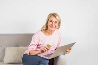Aged smiling woman in rose blouse with plastic card and laptop on sofa