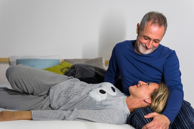 Aged smiling woman lying on man legs on bed
