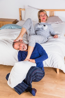 Aged smiling woman with legs on man with pillow near bed