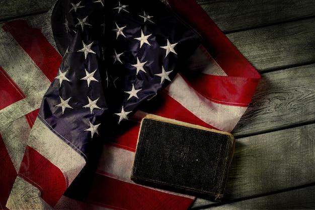 熟成したアメリカの国旗と本。国旗の横にある本。法律はあなたを守ります。神に誓って。