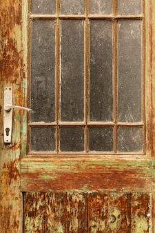 Aged vintage door with worn wood and glass