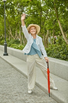 Aged white pretty travelling woman in casual cloth is standing near road and waving hand and smiling.
