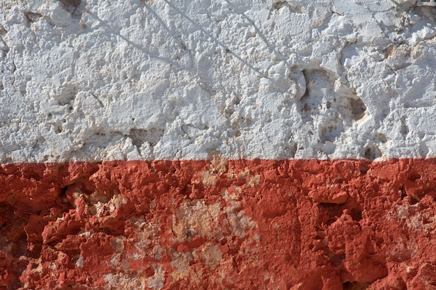 Aged whitewashed wall with red grunge paint