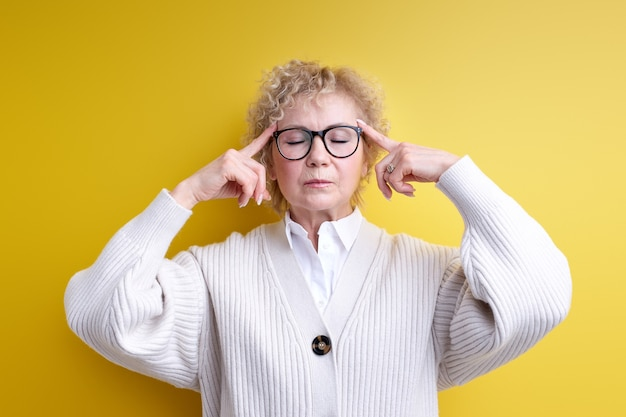 Aged woman feeling confused or doubting concentrating on an idea thinking hard with eyes closed