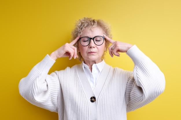Пожилая женщина смущена или сомневается, концентрируясь на идее, напряженно размышляя с закрытыми глазами