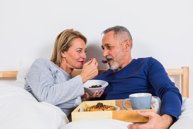 Aged woman giving berries to man in duvet near breakfast on tray on bed