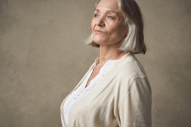 Пожилая женщина в моде халат позирует бабушке Premium Фотографии