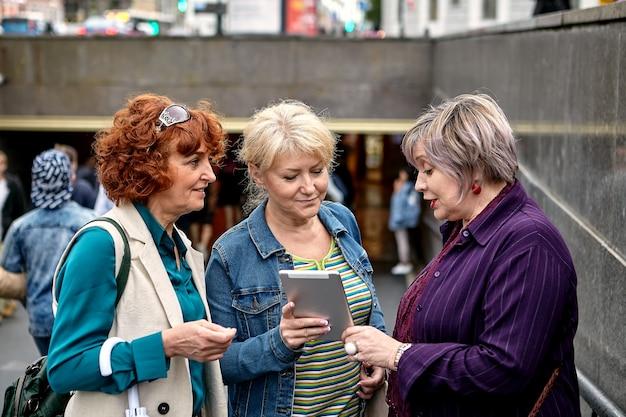 노인 여성이 지하도 근처의 여자 친구에게 태블릿 pc 화면에 사진을 보여주고있다.