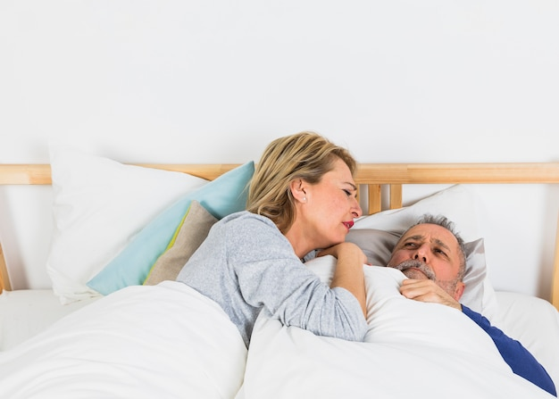 Aged woman lying near sad man in duvet on bed