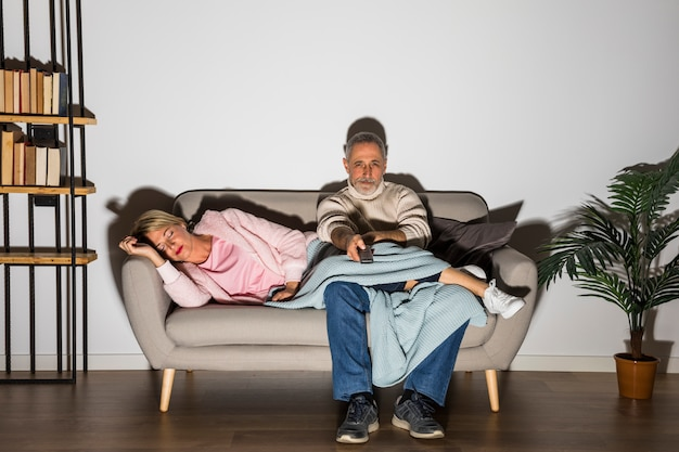 Aged woman and man with tv remote watching tv on settee